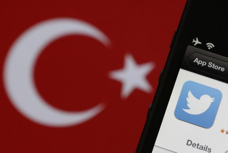 A Twitter logo on an iPhone display is pictured next to a Turkish flag in this photo illustration taken in Istanbul March 21, 2014. REUTERS/Murad Sezer