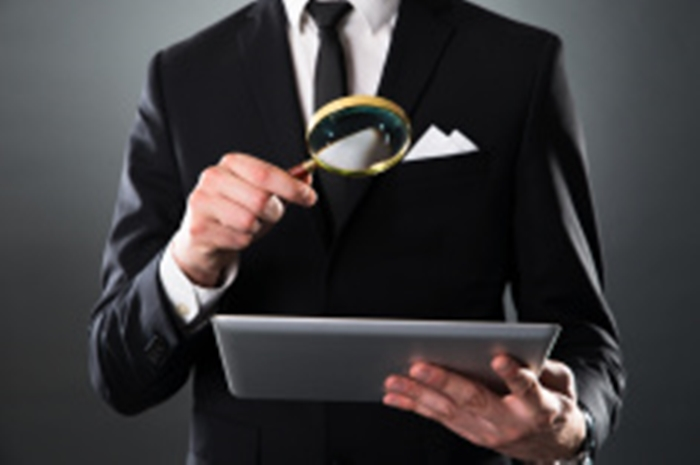 Businessman Analyzing Digital Tablet With Magnifying Glass stock photo